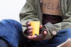 Χέρια των αστέγων με ένα φλυτζάνι εγγράφου στοκ φωτογραφίες
