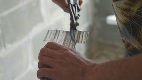 Χέρια των ατόμων που κόβουν το πλαίσιο για τον ξηρό τοίχο υποστηριγμάτων στα ατελή διαμερίσματα απόθεμα βίντεο
