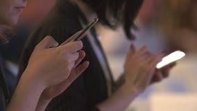 Χέρια των γυναικών που γράφουν στα τηλέφωνά τους σε μια διάσκεψη φιλμ μικρού μήκους