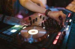 Χέρια των διάφορων ελέγχων διαδρομής τσιμπημάτων του DJ γυναικών στη λέσχη γεφυρών του DJ ` s τη νύχτα Στοκ εικόνα με δικαίωμα ελεύθερης χρήσης