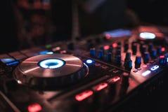 Χέρια των διάφορων ελέγχων διαδρομής τσιμπημάτων του DJ γυναικών στη λέσχη γεφυρών του DJ ` s τη νύχτα Στοκ Εικόνες