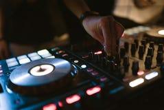Χέρια των διάφορων ελέγχων διαδρομής τσιμπημάτων του DJ γυναικών στη λέσχη γεφυρών του DJ ` s τη νύχτα Στοκ φωτογραφίες με δικαίωμα ελεύθερης χρήσης