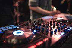 Χέρια των διάφορων ελέγχων διαδρομής τσιμπημάτων του DJ γυναικών στη λέσχη γεφυρών του DJ ` s τη νύχτα Στοκ Φωτογραφίες