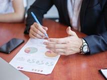 Χέρια των επιχειρηματιών σε έναν πίνακα πίσω από τα έγγραφα Στοκ εικόνα με δικαίωμα ελεύθερης χρήσης