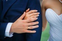 Χέρια των εραστών της νύφης και του νεόνυμφου γαμήλιο λευκό δαχτυλιδιών ανασκόπησης ανοιχτό Στοκ Εικόνα