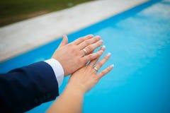 Χέρια των εραστών της νύφης και του νεόνυμφου γαμήλιο λευκό δαχτυλιδιών ανασκόπησης ανοιχτό Στοκ φωτογραφία με δικαίωμα ελεύθερης χρήσης