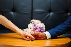 Χέρια των εραστών της νύφης και του νεόνυμφου γαμήλιο λευκό δαχτυλιδιών ανασκόπησης ανοιχτό Στοκ Φωτογραφία