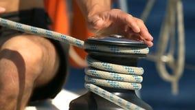 Χέρια των ιστιοπλοών που τυλίγουν το σχοινί στα μαύρα bitts στη βάρκα απόθεμα βίντεο