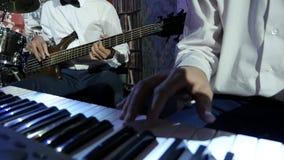 Χέρια των μουσικών στα άσπρα πουκάμισα που παίζουν μια ζωντανή συναυλία απόθεμα βίντεο