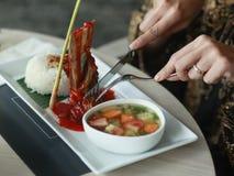 Χέρια των νέων γυναικών που προετοιμάζονται να φάει τα πλευρά βόειου κρέατος μελιού Στοκ Εικόνα