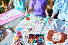 Χέρια των παιδιών που χρωματίζουν στην κατηγορία τέχνης στοκ φωτογραφία