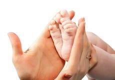 Χέρια των ποδιών λαβής μητέρων το μωρό σε ένα λευκό Στοκ φωτογραφία με δικαίωμα ελεύθερης χρήσης