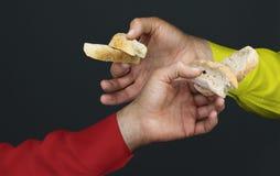 Χέρια δύο ατόμων με δύο peaces ενός άσπρου ψωμιού Στοκ Εικόνες
