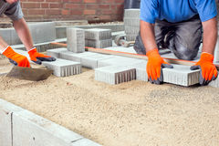 Χέρια δύο οικοδόμων που βάζουν τις πέτρες επίστρωσης Στοκ Εικόνα