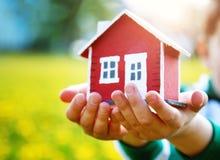 Χέρια Childs που κρατούν το κόκκινο πρότυπο σπίτι Στοκ φωτογραφία με δικαίωμα ελεύθερης χρήσης