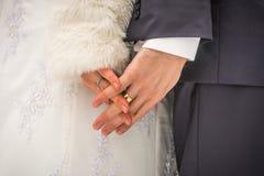 Χέρια Clasped της νύφης και του νεόνυμφου με τα δαχτυλίδια το χειμώνα Στοκ Φωτογραφία
