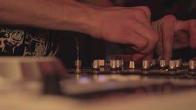 Χέρια Deejay που ωθούν και που γυρίζουν τα κουμπιά στην κονσόλα μίξης nightclub απόθεμα βίντεο