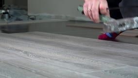 Χέρια Handyman που καθορίζουν τους φυλλόμορφους ξύλινους πίνακες δαπέδων απόθεμα βίντεο