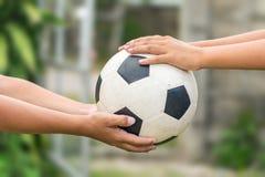 Χέρια Kid's που κρατούν το παλαιό ποδόσφαιρο στοκ φωτογραφίες