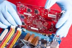 Χέρια Repairmans που τοποθετούν την τηλεοπτική κάρτα στο mainboard στο PC Στοκ Εικόνες