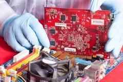 Χέρια Repairmans που τοποθετούν την τηλεοπτική κάρτα στο mainboard στο PC Στοκ φωτογραφία με δικαίωμα ελεύθερης χρήσης