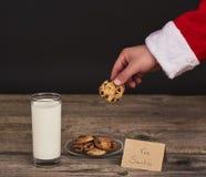 Χέρια Santa που κρατούν το μπισκότο σοκολάτας πέρα από το σκοτεινό ξύλινο πίνακα Στοκ Φωτογραφία