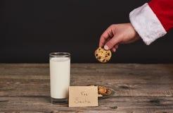 Χέρια Santa που κρατούν το μπισκότο σοκολάτας πέρα από το σκοτεινό ξύλινο πίνακα στοκ φωτογραφία με δικαίωμα ελεύθερης χρήσης
