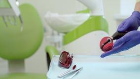 Χέρια Stomatolog που προετοιμάζουν το λαμπτήρα πολυμερισμού για τη στοματική κοιλότητα απόθεμα βίντεο