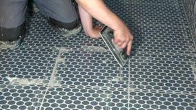 Χέρια tiler των γεμίζοντας χασμάτων εργαζομένων μεταξύ των κεραμιδιών με ένα ρευστοκονίαμα φιλμ μικρού μήκους