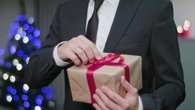 Χέρια Unwrapping ατόμων ` s ένα δώρο Χριστουγέννων απόθεμα βίντεο