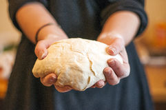Χέρια Woomens που κρατούν την τελειωμένη καθαρή ζύμη στοκ φωτογραφία με δικαίωμα ελεύθερης χρήσης