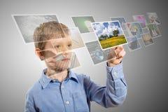 Χέρι αγοριών που φθάνει στις εικόνες που ρέουν από το βαθύ. στοκ εικόνα με δικαίωμα ελεύθερης χρήσης
