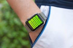 Χέρι αθλητών με το ρολόι της Apple και app Workout στην οθόνη Στοκ Εικόνες