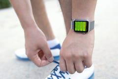 Χέρι αθλητών με το ρολόι της Apple και app Workout στην οθόνη Στοκ Φωτογραφίες