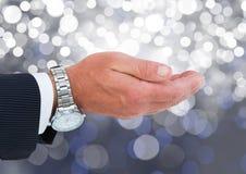Χέρι ανοικτό με το πλούσιο ρολόι με το λαμπιρίζοντας ελαφρύ υπόβαθρο bokeh Στοκ Εικόνες