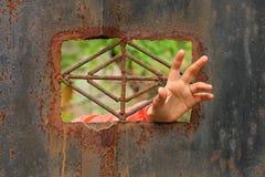 Χέρι από ένα παράθυρο φυλακών που απαιτεί τη βοήθεια Στοκ Εικόνα