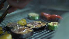 Χέρι αρχιμαγείρων που γυρίζει στην άλλη δευτερεύουσα μελιτζάνα ντοματών λαχανικών, κολοκύθια, κίτρινο πιπέρι κουδουνιών στη σχάρα απόθεμα βίντεο