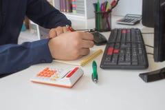 Χέρι ατόμων με τη μάνδρα, τον υπολογιστή και τον υπολογιστή στον ξύλινο πίνακα Χρησιμοποιεί τον υπολογιστή του και γράφει τους αρ Στοκ εικόνα με δικαίωμα ελεύθερης χρήσης