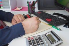 Χέρι ατόμων με τη μάνδρα, τον υπολογιστή και τον υπολογιστή στον ξύλινο πίνακα Χρησιμοποιεί τον υπολογιστή του και γράφει τους αρ Στοκ Εικόνες
