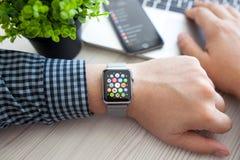 Χέρι ατόμων με το ρολόι της Apple και app εικονίδιο στην οθόνη Στοκ Φωτογραφία