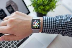 Χέρι ατόμων με το ρολόι της Apple και app εικονίδιο στην οθόνη Στοκ φωτογραφίες με δικαίωμα ελεύθερης χρήσης