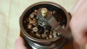 Χέρι ατόμων που αλέθει τον ψημένο καφέ στον παλαιό αναδρομικό μύλο απόθεμα βίντεο