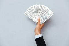 Χέρι ατόμων που κρατά τα αμερικανικά δολάρια Στοκ Εικόνες
