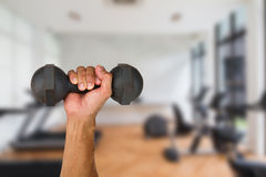 Χέρι ατόμων που κρατά τον παλαιό αλτήρα στο θολωμένο υπόβαθρο γυμναστικής στοκ φωτογραφία με δικαίωμα ελεύθερης χρήσης