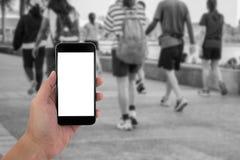 Χέρι ατόμων που κρατά το τηλέφωνο και την άσπρη οθόνη με το Μαύρο θαμπάδων και Στοκ εικόνα με δικαίωμα ελεύθερης χρήσης