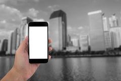 Χέρι ατόμων που κρατά το τηλέφωνο και την άσπρη οθόνη με το Μαύρο θαμπάδων και Στοκ Εικόνες