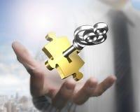 Χέρι ατόμων που παρουσιάζει χρυσό κομμάτι γρίφων με το ασημένιο κλειδί στοκ εικόνα με δικαίωμα ελεύθερης χρήσης