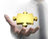 Χέρι ατόμων που παρουσιάζει χρυσό κομμάτι γρίφων στοκ εικόνες
