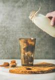 Χέρι ατόμων ` s έτοιμο να χύσει το γάλα στους παγωμένους κύβους καφέ Στοκ Εικόνες