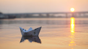 Χέρι ατόμων ` s που βάζει τη βάρκα εγγράφου στο νερό και που ωθεί την μακριά κατά τη διάρκεια του όμορφου ηλιοβασιλέματος με τον  Στοκ εικόνα με δικαίωμα ελεύθερης χρήσης